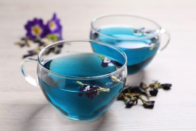 Glass cups of organic blue Anchan on white wooden table, closeup. Herbal tea