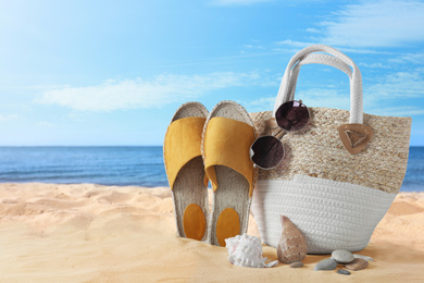Beach objects on sand near sea, space for text. Summer vacation