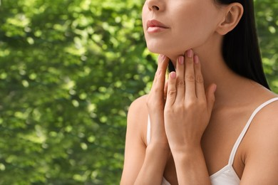 Young woman doing thyroid self examination near window, closeup. Space for text