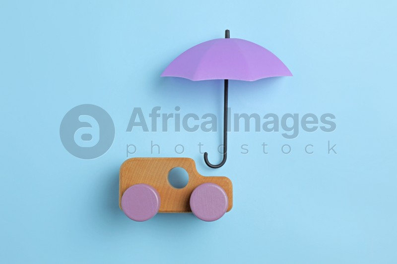 Bright umbrella and toy car on light blue background, flat lay