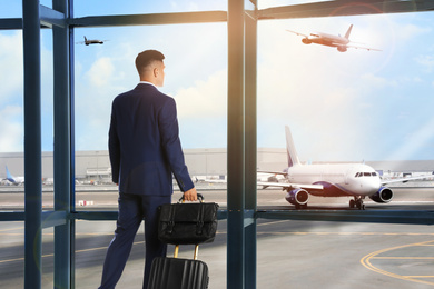 Businessman with bag and travel suitcase at airport terminal. Summer vacation