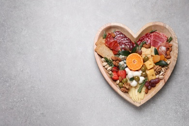 Heart shaped plate with different delicious snacks on grey table, top view. Space for text