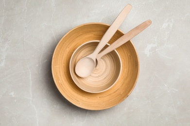 Wooden spoons in bowls on grey table, top view. Cooking utensils
