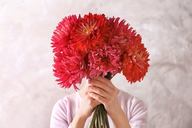 Woman hiding behind beautiful dahlia flowers on color background