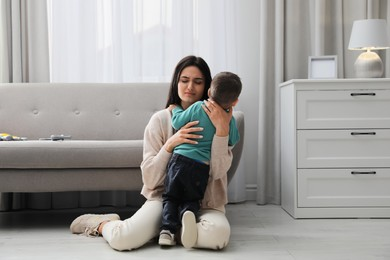 Depressed single mother with child in living room