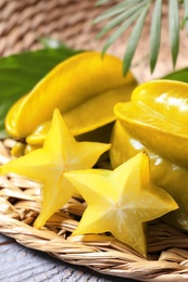 Delicious carambola fruits on light grey wooden table