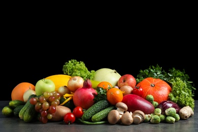 Assortment of fresh organic fruits and vegetables on grey table