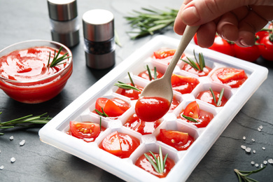 Woman pouring sauce into ice cube tray with tomatoes and rosemary at grey table, closeup