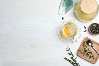 Aromatic eucalyptus tea on white wooden table, flat lay. Space for text