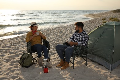 Couple with hot drinks near camping tent on beach
