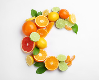 Letter C made with citrus fruits on white background as vitamin representation, top view