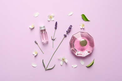 Flat lay composition with elegant perfume on lilac background