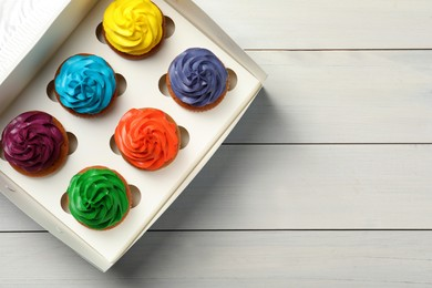 Box with different cupcakes on white wooden table, top view. Space for text