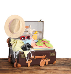 Open vintage suitcase with different beach objects packed for summer vacation on wooden table against white background