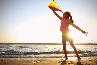 Cute little child playing with kite on beach near sea at sunset. Spending time in nature