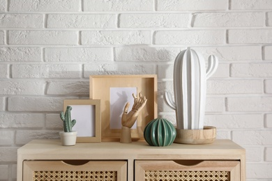 Different accessories on wooden cabinet near white brick wall indoors. Interior design