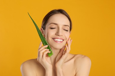 Happy young woman with aloe leaf on yellow background
