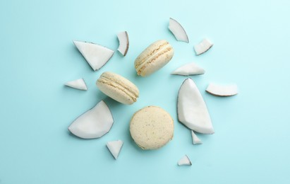 Flat lay composition with macarons and pieces of coconut on light blue background