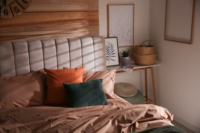 Bed with stylish linen and soft pillows in room