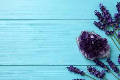 Amethyst, lavender and space for text healing herbs on light blue wooden table, flat lay.