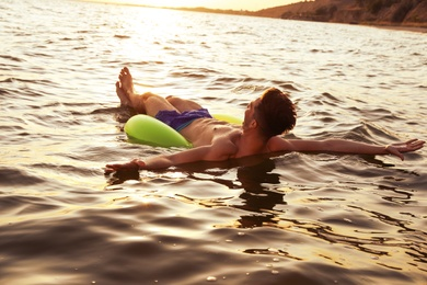 Young man with inflatable ring in sea