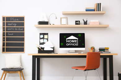 Modern computer with text HOME OFFICE on wooden table indoors