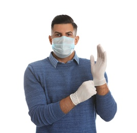 Man in protective face mask putting on medical gloves against white background