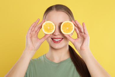Young woman with cut lemon on yellow background. Vitamin rich food