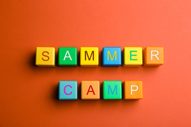 Colorful wooden cubes with phrase SUMMER CAMP on red background, flat lay