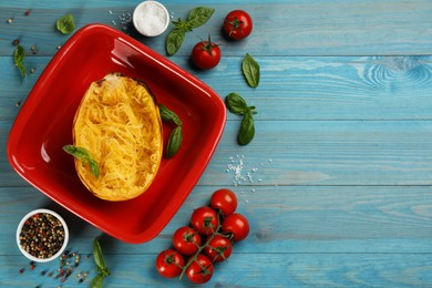 Half of cooked spaghetti squash in baking dish and ingredients on turquoise wooden table, flat lay. Space for text