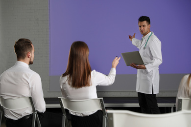 Male doctor with laptop giving lecture in conference room with projection screen