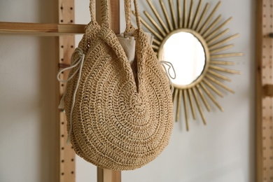 Stylish woman's bag hanging on rack in boutique