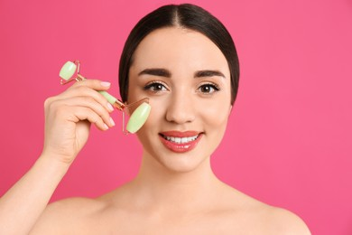 Woman using natural jade face roller on pink background