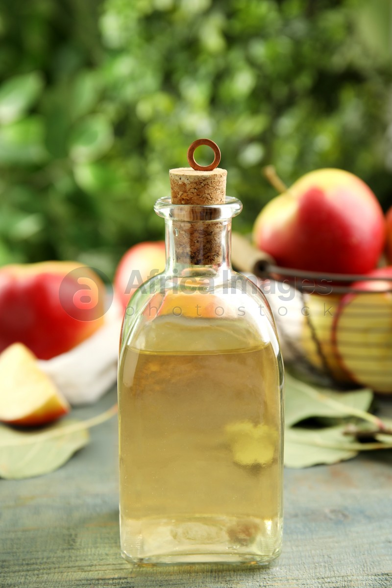 Natural apple vinegar and fresh fruits on blue wooden table