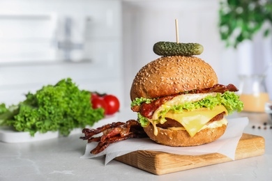 Fresh juicy bacon burger on grey table. Space for text