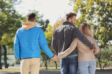 Woman holding hands with another man behind her boyfriend's back during walk in park. Love triangle