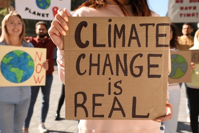 Woman with poster protesting against climate change outdoors, closeup