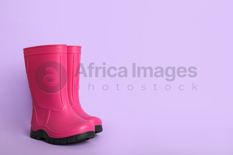 Bright pink rubber boots on violet background. Space for text