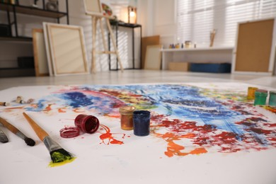 Paints and brushes on abstract picture in art studio with easel