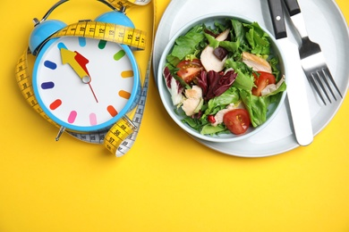 Plate of tasty salad, alarm clock and measuring tape on yellow background, flat lay with space for text. Nutrition regime
