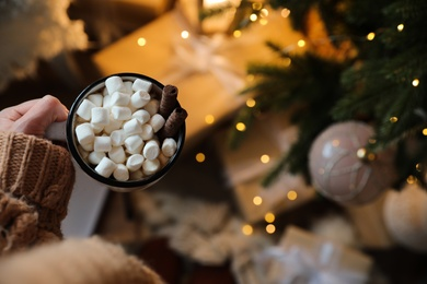 Woman with cup of cocoa indoors, top view. Christmas mood