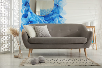 Stylish living room with blue flowers painted on wall. Floral pattern in interior design