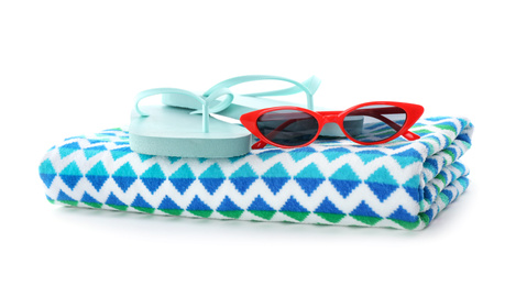 Bright towel, sunglasses and flip flops on white background. Beach objects