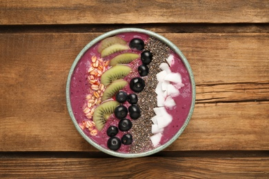 Healthy breakfast with delicious acai smoothie and fruits in bowl on wooden table, top view