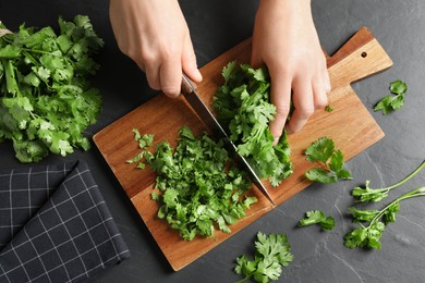 Woman cutting fresh green cilantro at black table, top view