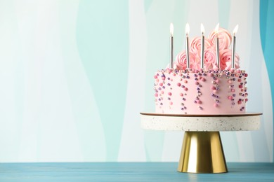 Beautifully decorated birthday cake on turquoise wooden table, space for text
