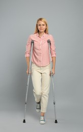 Young woman with axillary crutches on grey background