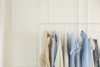 Rack with stylish women's clothes near white wall. Interior design