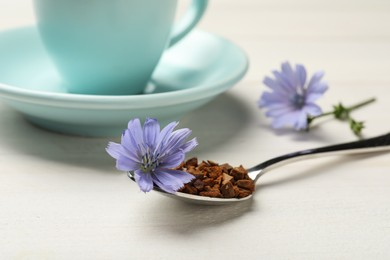 Spoon of chicory granules with flower on white wooden table, closeup