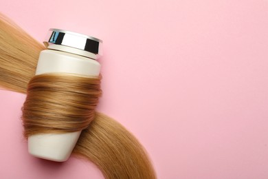 Bottle wrapped in lock of hair on pink background, top view with space for text. Natural cosmetic product